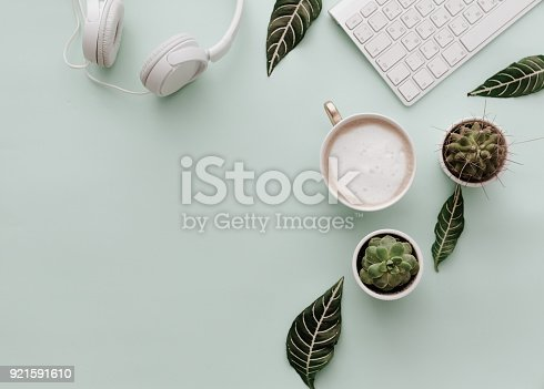 istock Neutral Minimalist Flat Lay Scene With coffee, keyboard, headphones and cactus 921591610