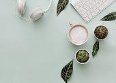 istock Neutral Minimalist Flat Lay Scene With coffee, keyboard, headphones and cactus 921591610