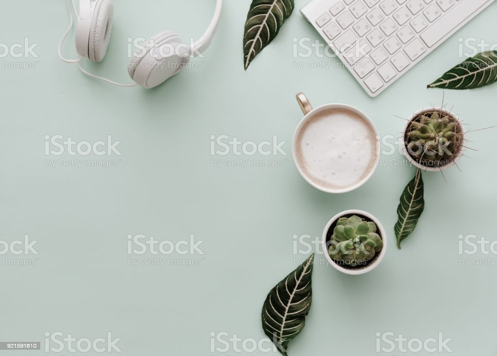 Cтоковое фото Neutral Minimalist Flat Lay Scene With coffee, keyboard, headphones and cactus