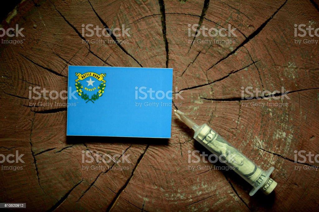 Bandeira de Nevada em um toco com seringa, injetando dinheiro na bandeira - foto de acervo