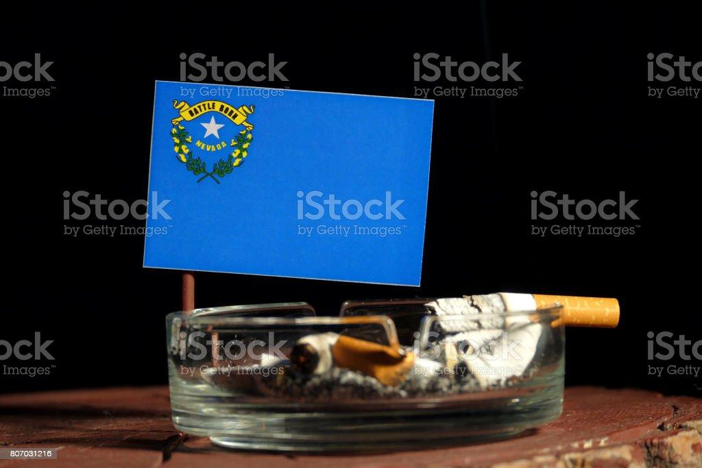 Bandeira de Nevada com queima de cigarro no cinzeiro isolado no fundo preto - foto de acervo