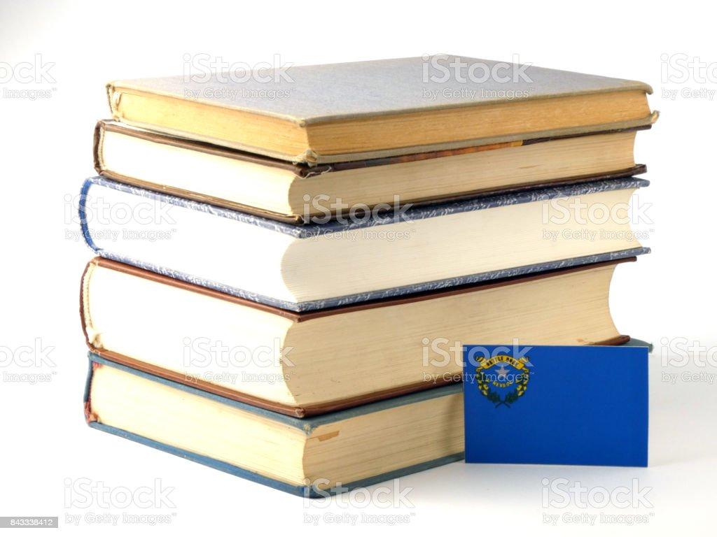 Bandeira de Nevada com pilha de livros isolado no fundo branco - foto de acervo