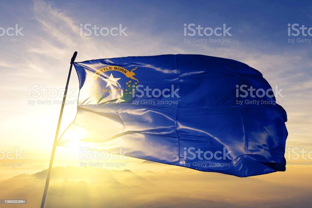 Nevada estado dos Estados Unidos bandeira pano tecido têxtil acenando do nevoeiro de névoa superior ao nascer do sol - foto de acervo