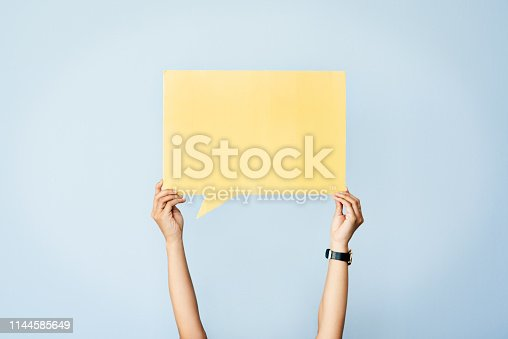 Shot of an unrecognizable woman holding up a speech bubble against a blue background