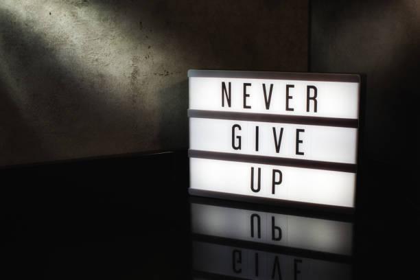 never give up motivierende botschaft auf einem leuchttisch - hindernisse überwinden stock-fotos und bilder