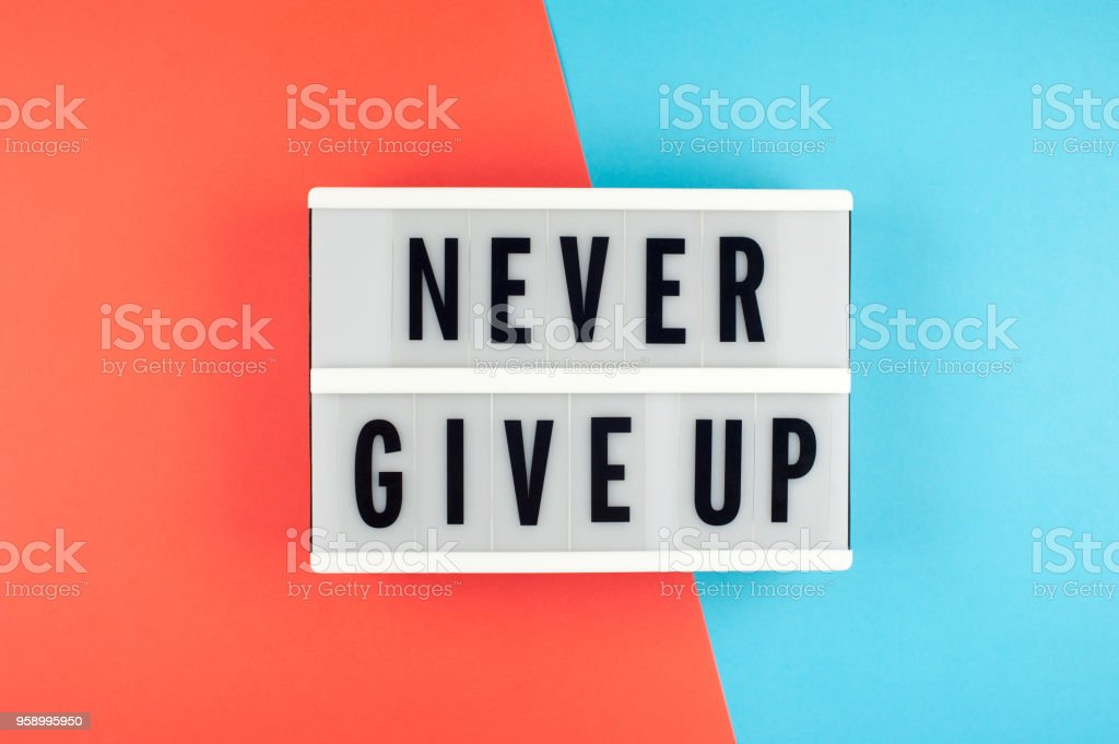 Never give up  - text on a display lightbox on blue and red bright background. stock photo