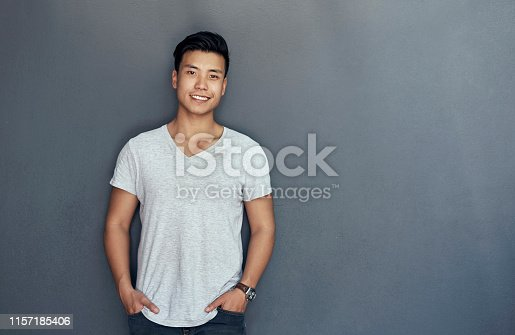 Studio portrait of a handsome young man posing against a grey background