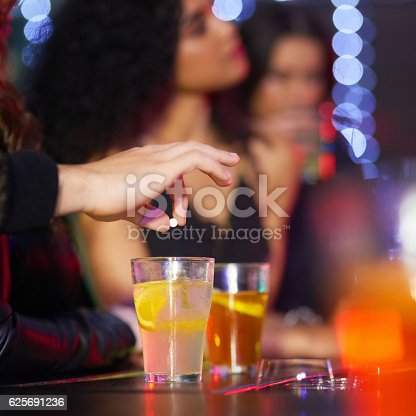 Closeup shot of a man drugging a woman's drink in a nightclub