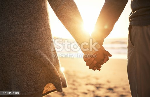 Rearview shot of an unrecognizable couple holding hands while at the beach