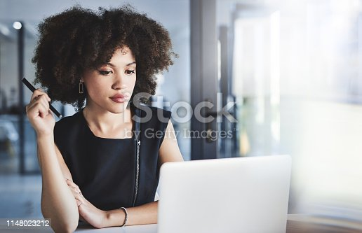 Shot of a beautiful young businesswoman working on a laptop in her office