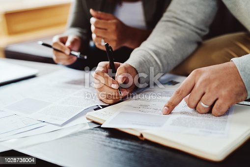 Closeup shot of an unrecognizable couple going through paperwork together at home