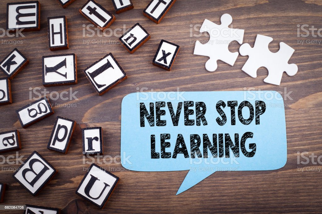 Never stop learning concept. Speech Bubble on a dark textured wooden background stock photo