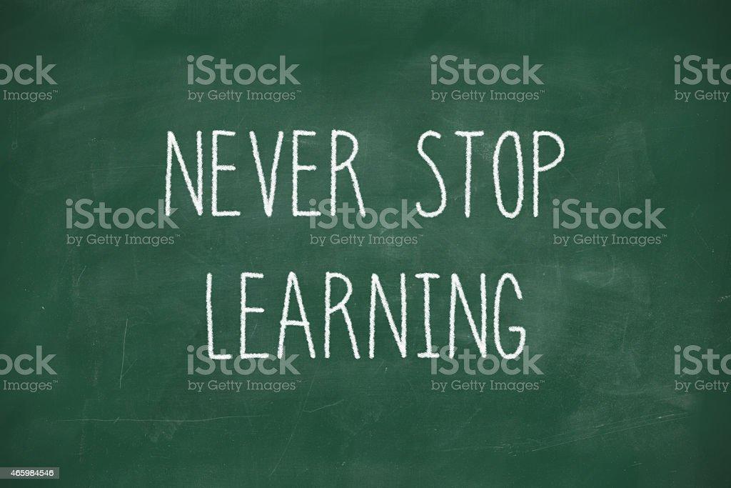 Never stop learning handwritten on blackboard stock photo