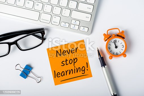 Never stop Learning - written message on white desk workplace. E-learning education concept.