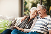 Shot of a happy senior couple relaxing together on a sofa outside at home