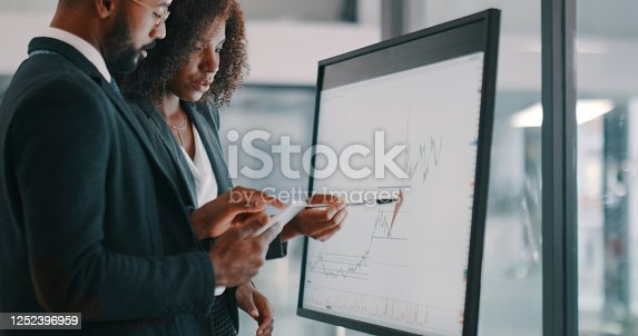 Shot of a young businessman and businesswoman using an interactive whiteboard to analyse data in a modern office