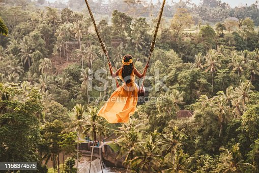 Photo of woman with long swing and forest view. Young woman swinging in the jungle rainforest of Bali island, Indonesia. Swing in the tropics. Women sit on swings at a height of more than twenty meters. In Indonesia Bali Province.