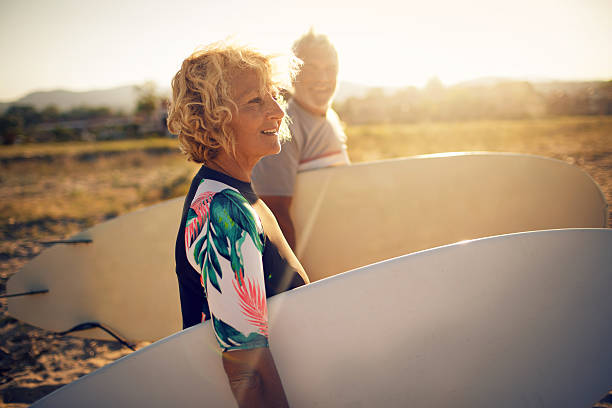 Never too old for surfing Very active senior couple getting ready to surf the waves on their active vacation leisure equipment stock pictures, royalty-free photos & images