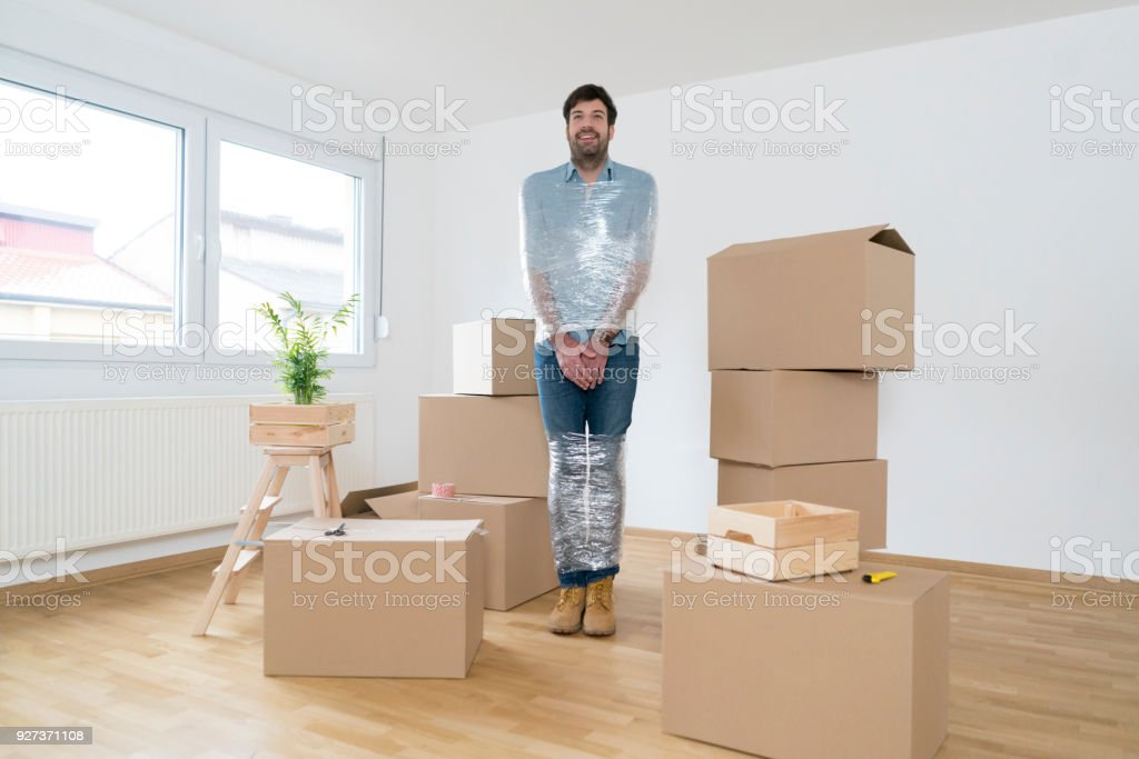 Never Trust Those Girls Again! Funny, young man standing among cardboard boxes wrapped with adhesive tape and trapped. Adult Stock Photo