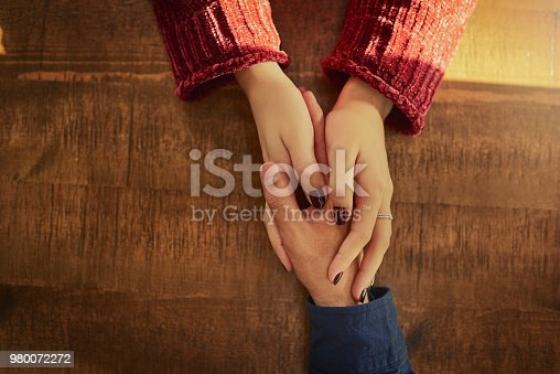 Cropped high angle shot of an unidentifiable man and woman holding hands on a table