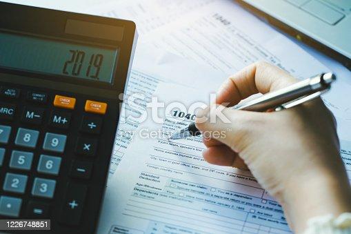 New 2019 IRS 1040 tax form.Closeup woman filling form of Individual Income Tax Return