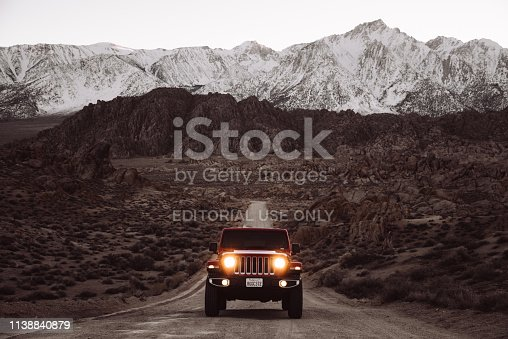 Lone Pine, California, United States - March 9, 2019: Photo of a Jeep Wrangler Sahara 2019 edition parked on a dirt road at the Alabama Hills close to the city of Lone Pine. It is the new wild offroad vehicle by Jeep. Headlights are on since the pic has been taken after the sunset.