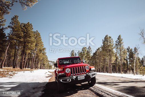 Kaibab National Forest, Arizona, United States - March 6, 2019: Photo of a Jeep Wrangler Sahara 2019 edition parked along the road in the Kaibab National Forest in Arizona. It is the new wild offroad vehicle by Jeep. Snow is present along the road.