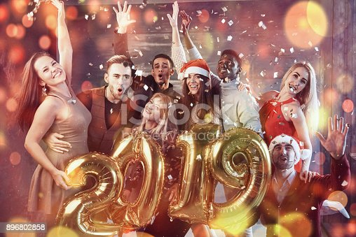 istock New 2019 Year is coming! Group of cheerful young multiethnic people in Santa hats carrying gold colored numbers and throwing confetti on the party 896802858