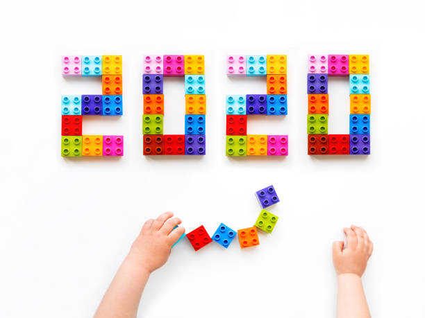 New 2020 Year. Child is playing with colorful constructor blocks. Kid's hands with bricks toy on white background. Educational toy, flat lay, top view. stock photo