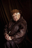 Rembrandt inspired portrait. A mature man is sitting against a studio background dressed in a 19th Centruty style looking at the camera while holding a paintbrush.