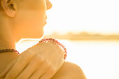 A young woman wearing crystal gemstone bracelet and necklace by the sea at dawn. Shot at Antibes Juan-les-Pins, Cote d'Azur, France.