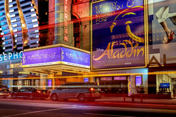 New Amsterdam Theatre showing Aladdin musical on Broadway New York City, United States - October 25, 2016: Night view with busy traffic light trails of the New Amsterdam Theatre showing Disney's Aladdin musical on Broadway in Manhattan theater marquee commercial sign stock pictures, royalty-free photos & images