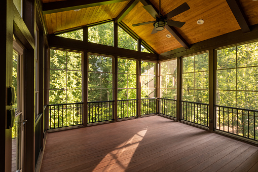 Modern screened porch enclosure with plastic windows and composite floor with summer woods in the background.