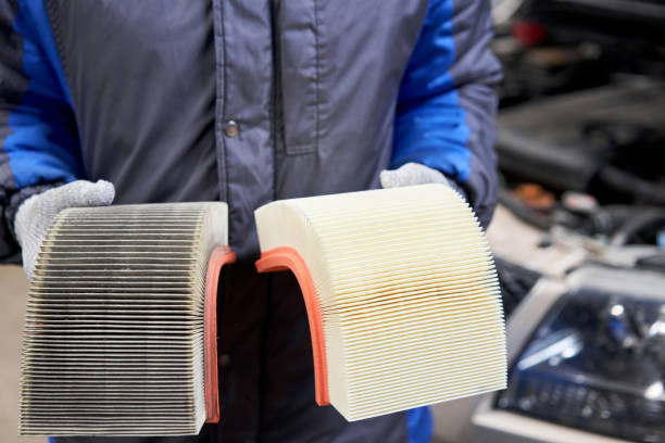 New and old dirty automotive engine air filter in the hands of an auto mechanic. Auto repair concept. stock photo