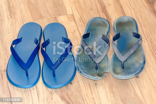 istock New and old dirty flip flops on light brown floor. Two pairs new and worn out shoes. Blue sandals isolated on wood background. Before and after concept 1157009087
