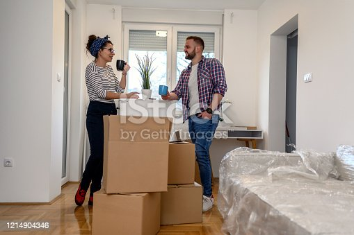 Couple Carrying Boxes Into New Home and drinking coffee
