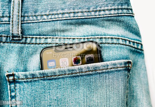 Paris, France - Nov 10, 2017: New Apple iPhone X smartphone telephone in the rear pockets of modern denim jeans pants