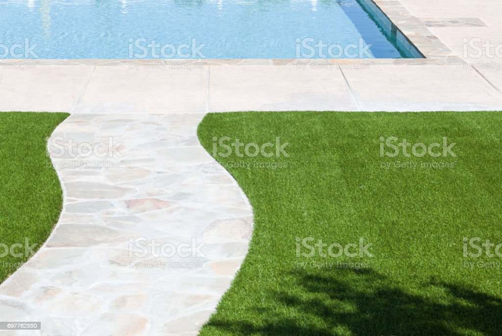 New Artificial Grass Installed Near Walkway and Pool. stock photo
