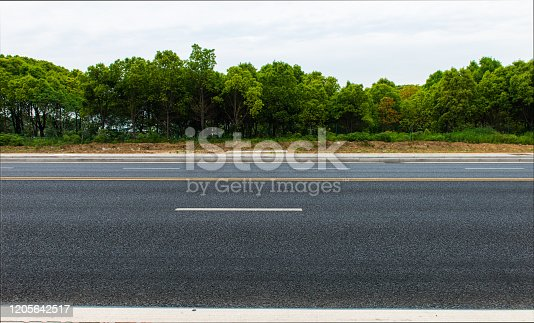 New asphalt roads, trees under blue sky and white clouds
