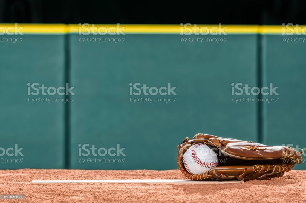 A new baseball in a glove on the pitcher's mound rubber stock photo
