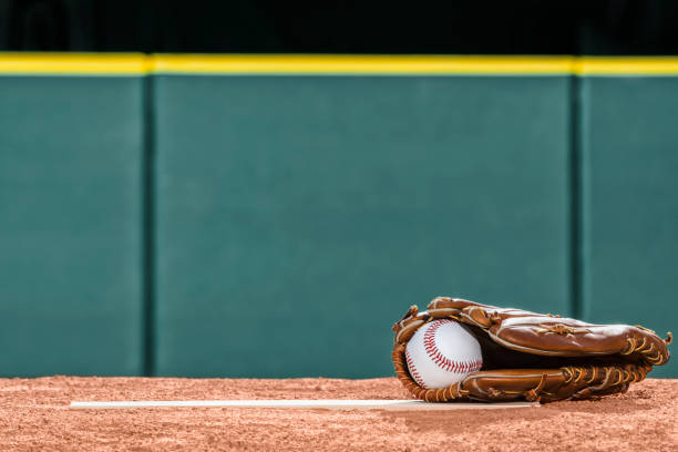 A new baseball in a glove on the pitcher's mound rubber A low angle view of a new baseball in a brown leather baseball glove sitting on the rubber of a pitcher's mound with a green padded wall and a dark green