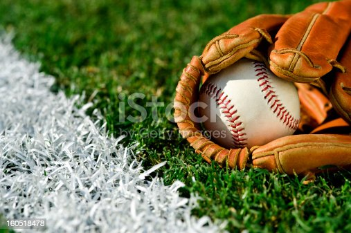 New Baseball inside a baseball glove on the outfield grass next to the foul line