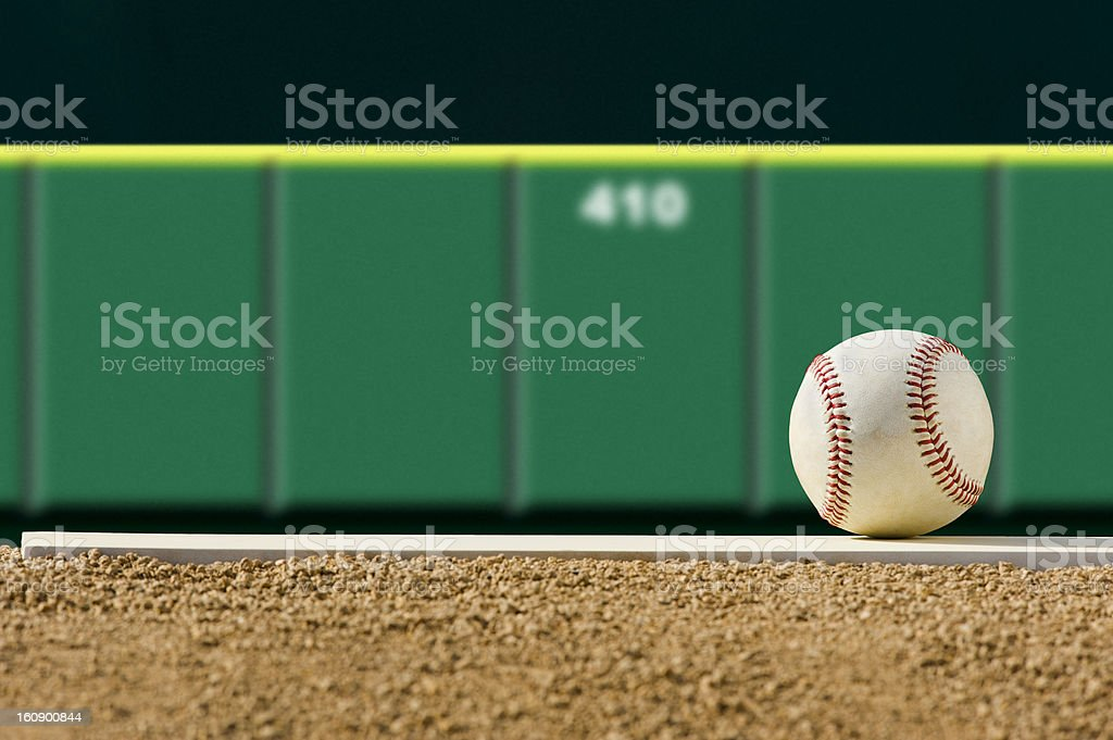 New Baseball on Pitcher's Mound, outfield wall stock photo