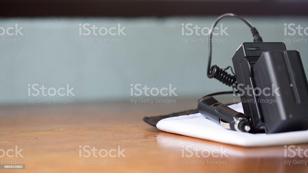 New battery charger on white sheet, including car adapter and battery. stock photo