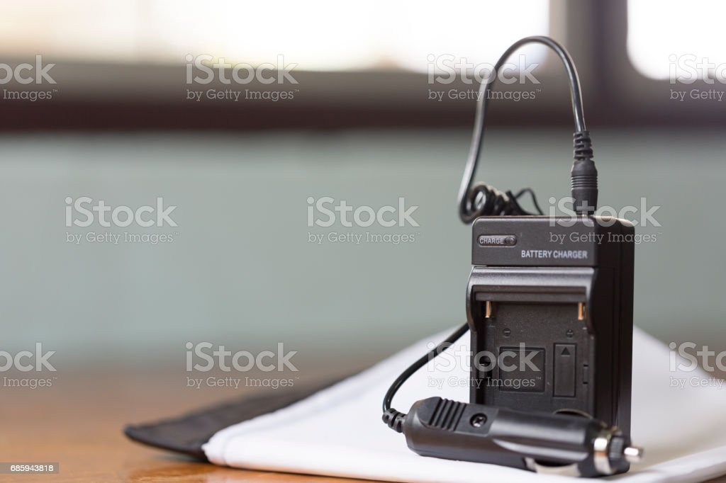 New battery charger on white sheet, including car adapter stock photo
