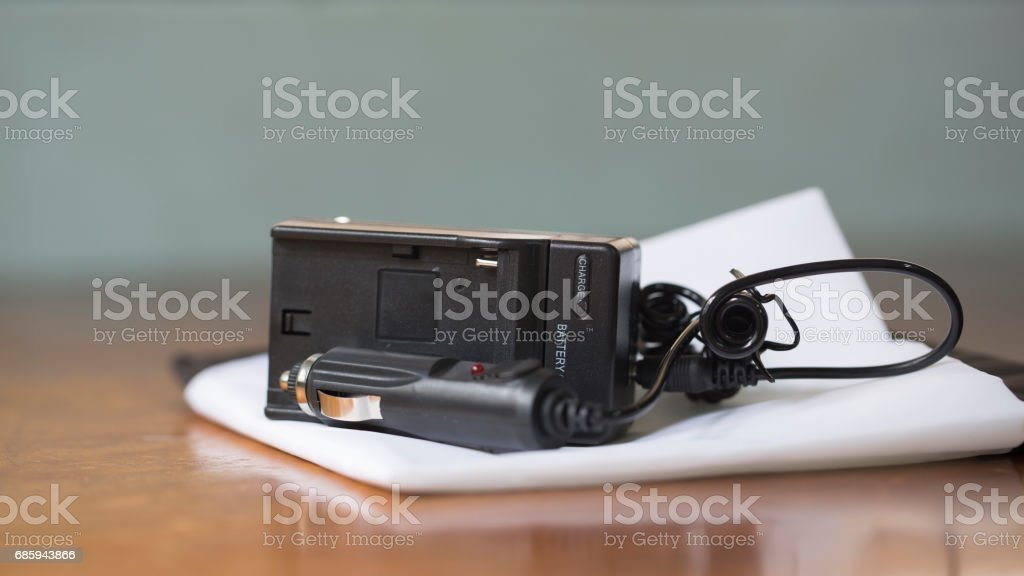 New battery charger on white sheet, including car adapter. stock photo
