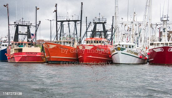 New Bedford, Massachusetts, USA-August 7, 2019- A few of the many brightly painted commercial commercial fishing trawlers docked in the very busy New Bedford harbor. New Bedford is one of the busiest fishing harbors in the world.