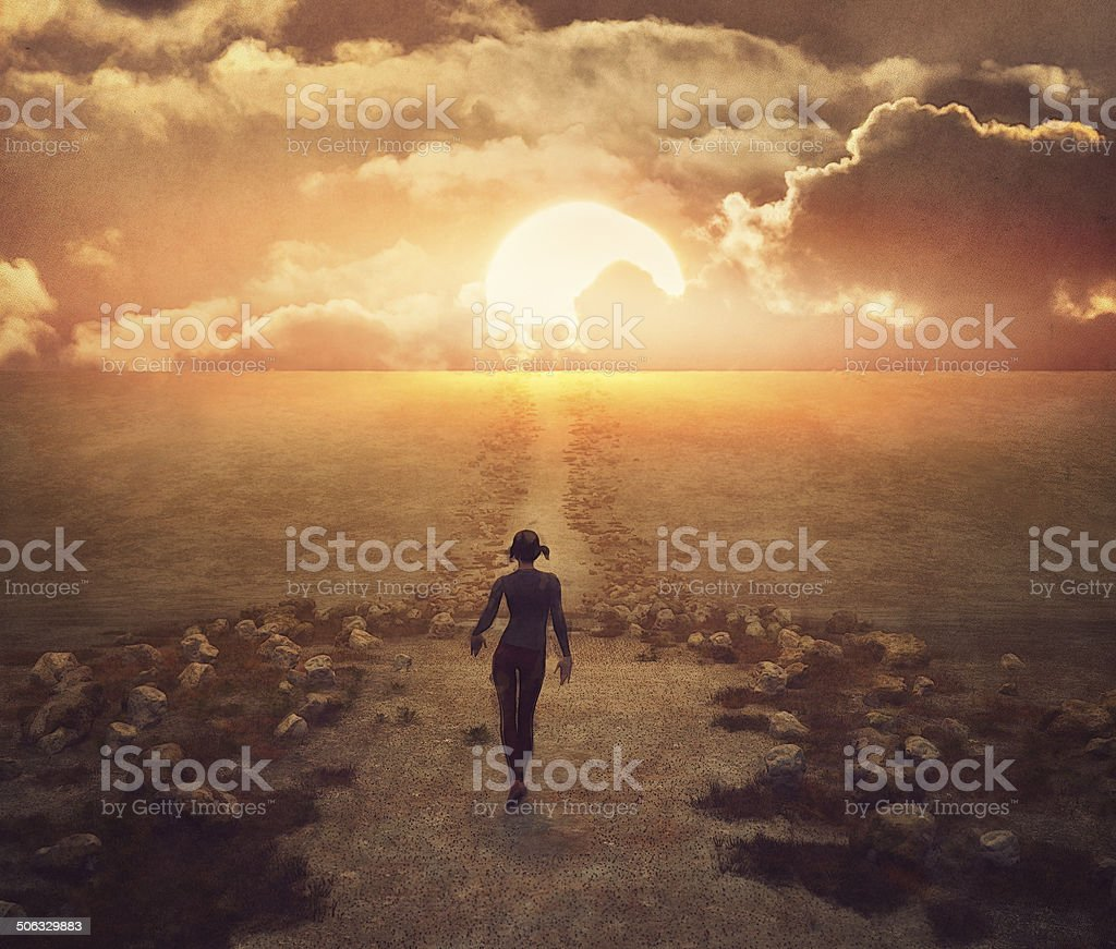 New beginning for young woman walking into the sunset stock photo