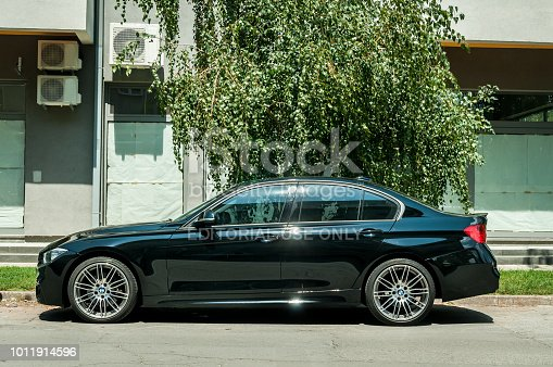 921871456 istock photo New black custom BMW 5 series with alloy wheels parked on the street 1011914596