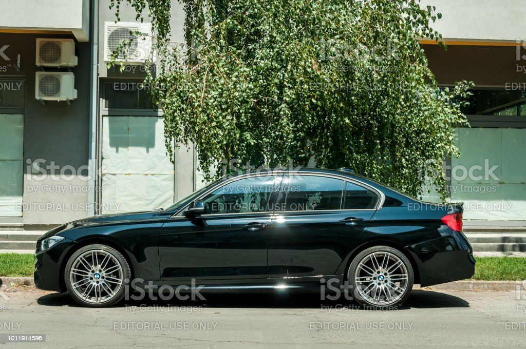 New black custom BMW 5 series with alloy wheels parked on the street stock photo